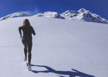 Photo of a woman in athletic apparel running up a snow-covered mountain.