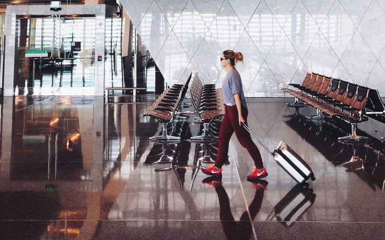 woman walking through airport with suitcase
